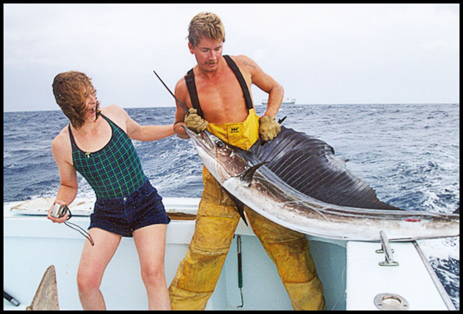 Capt. Rooks holding a sailfish while a woman angler watches