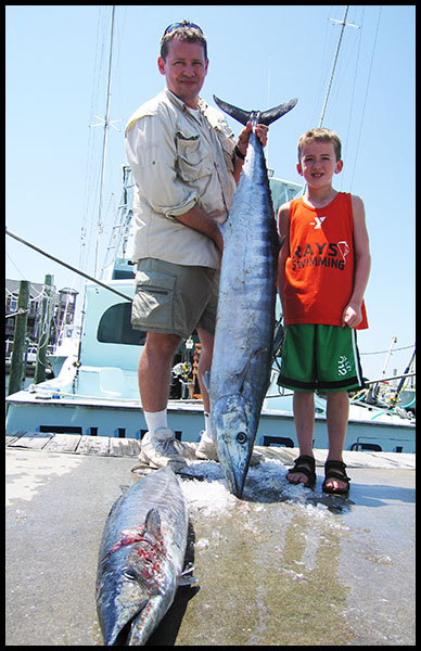 man and boy holding a wahoo