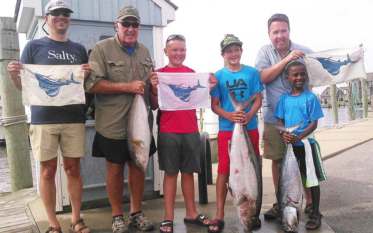 Hatteras deep sea fishing party holding sailfish release flags