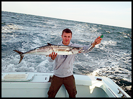 deep sea angler holding a king mackerel in Tuna Duck cockpit