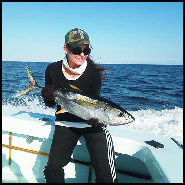 lady angler holds q yellowfin tuna on the stern of the Tuna Duck