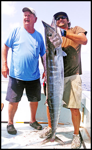 charter fisherman holding a very large wahoo